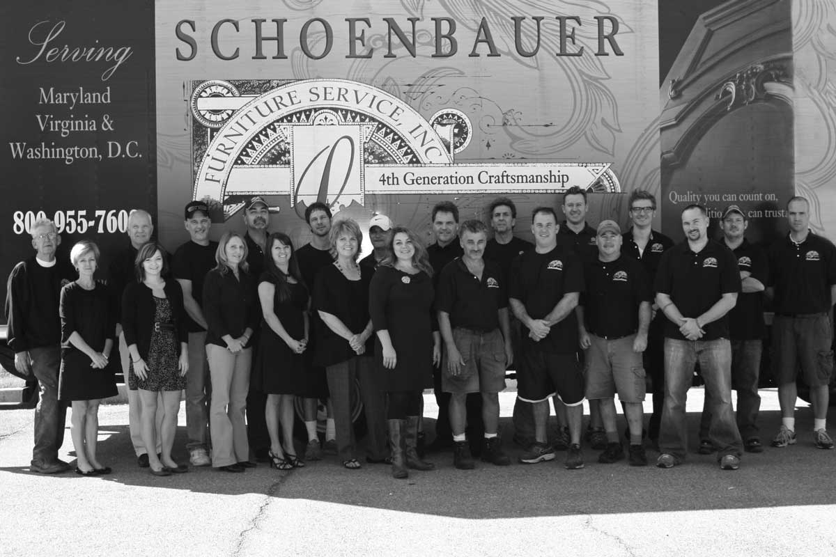 Schoenbauer team in front of sign